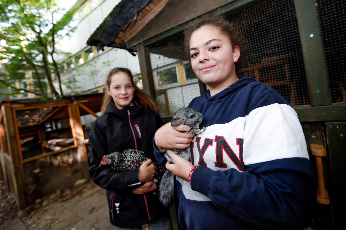 Bild zwei Schülerinnen mit Tieren aus dem Schulzoo